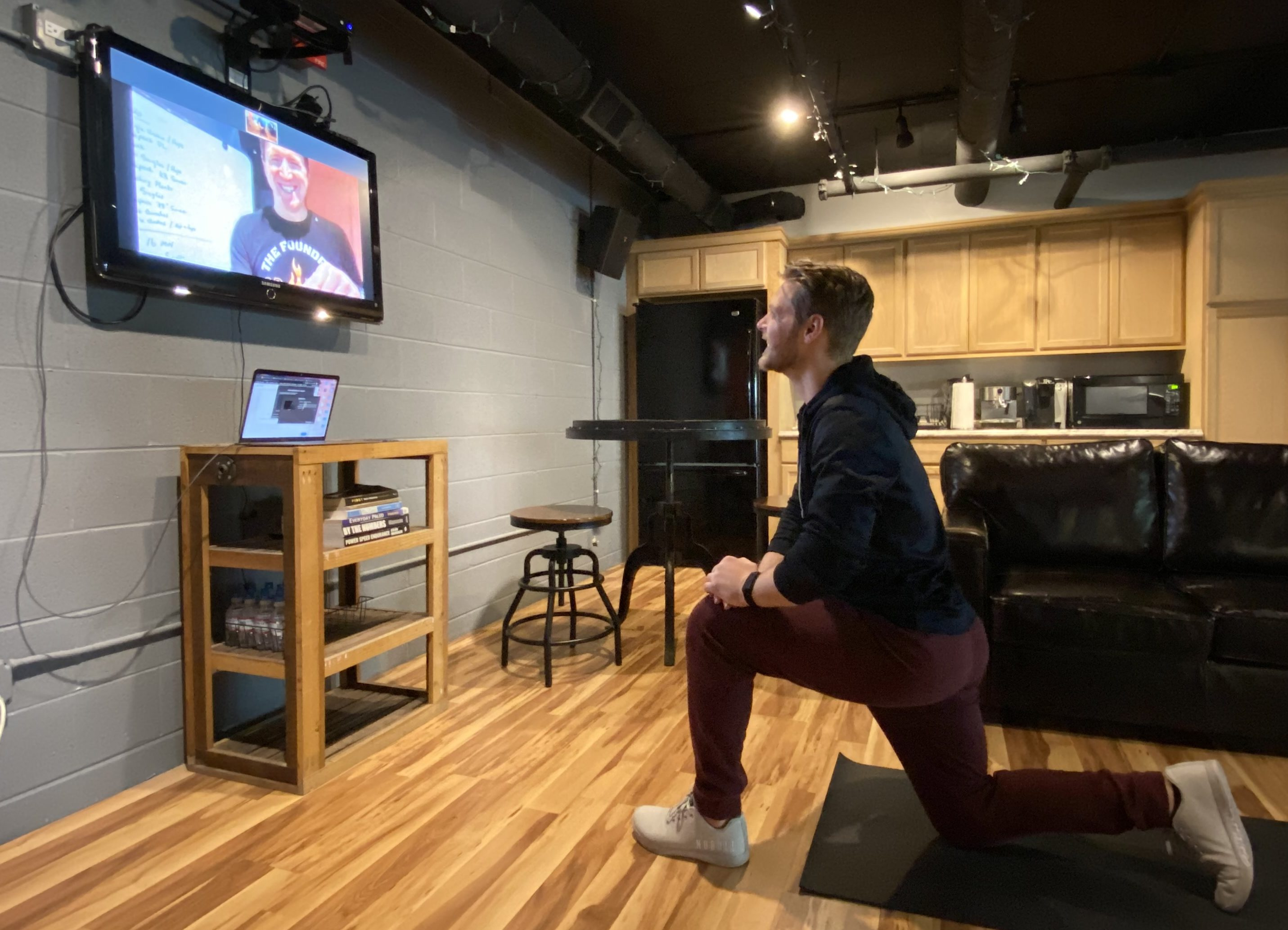 Image of a man doing an online group fitness class working out from home